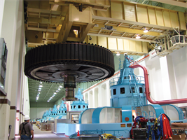 A contract worker watches as a crane moves a 1,200-ton rotor as part of McNary Lock and Dam's stator winding replacement near Umatilla, Ore. in August 2010.
